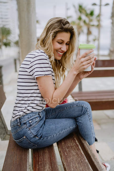 Side view of cheerful casual young woman drinking from takeaway cup of coffee sitting on city bench at seafront on summer day — Stock Photo