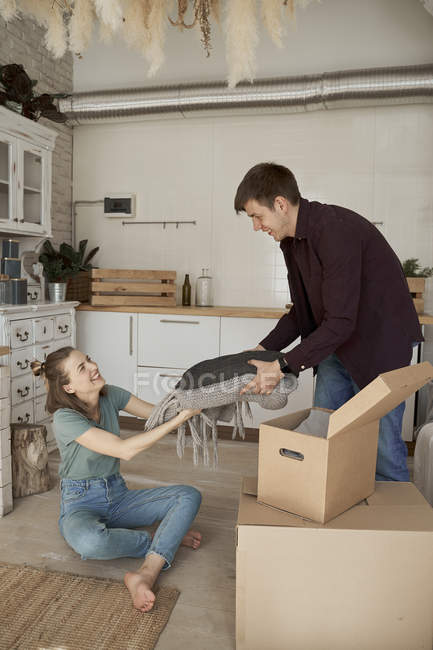 Happy young couple taking out things from boxes in white light kitchen — Stock Photo