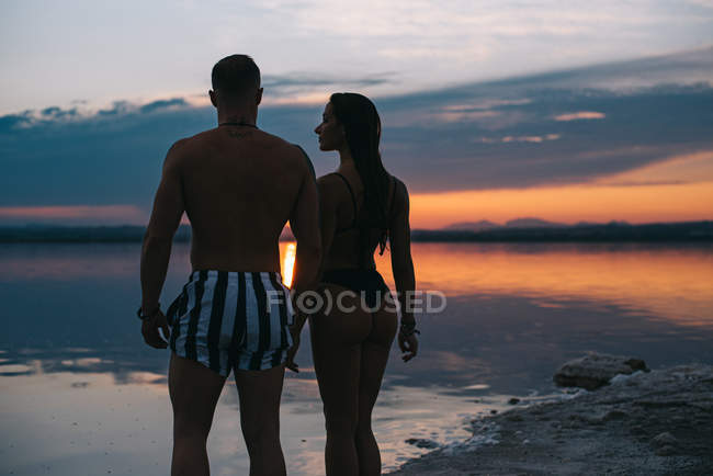 Back view of man and woman on vacation standing in embrace on majestic beach with vibrant crimson sunset sky on background at Torrevieja at Spain — Stock Photo