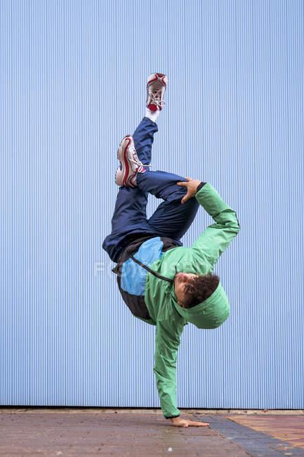 Coole lockige männliche Tänzerin in Sportbekleidung und Turnschuhen macht Handstand mit Schneidersitz gegen blaue Wand auf der Straße — Stockfoto