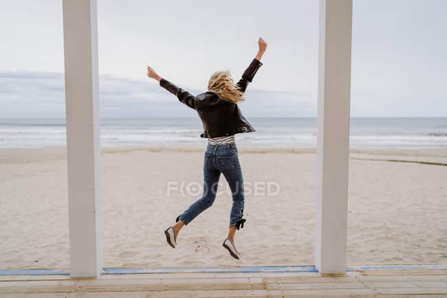 Visão traseira da mulher na moda em jaqueta preta saltando alegremente com braços levantados no cais de madeira branca com oceano no fundo — Fotografia de Stock