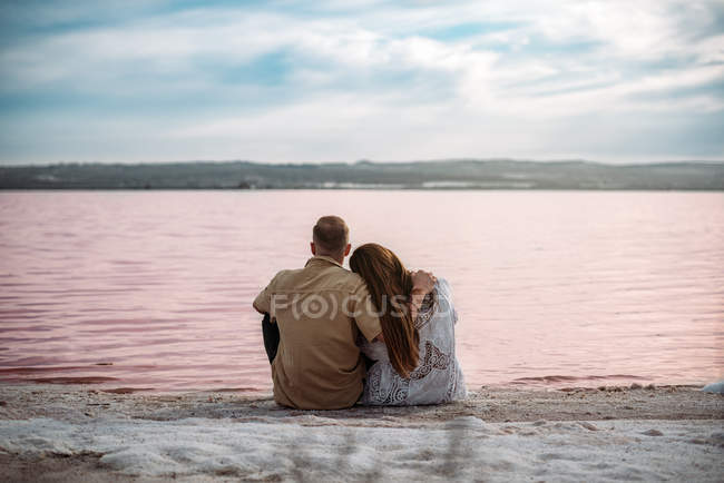 Back view of couple sitting on an amazing beach of pink water and blue sky holding hands — Stock Photo