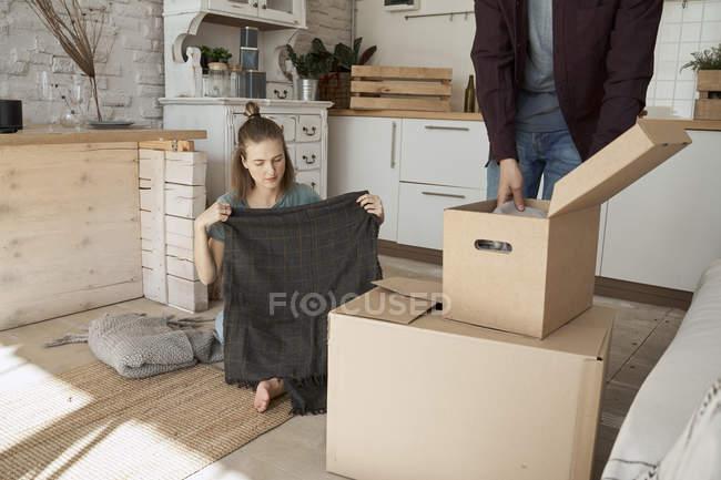 Feliz pareja joven que saca las cosas de las cajas de cartón en la cocina ligera blanca. - foto de stock