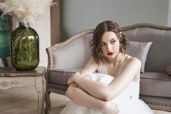 Superbe femme avec des lèvres rouges en robe blanche regardant loin tout en étant assis sur le sol à côté du canapé — Photo de stock