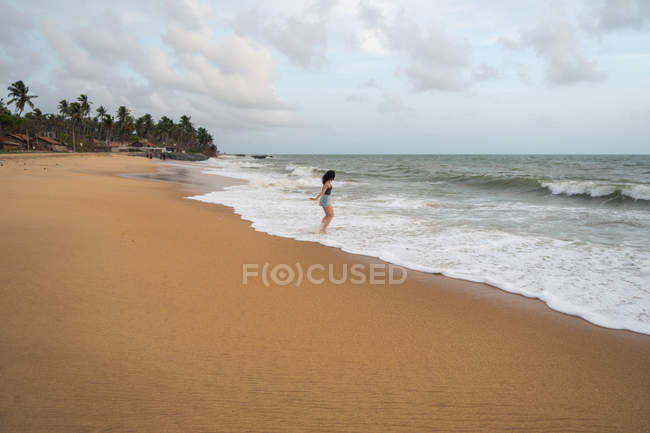 Woman in beachwear walking on sand barefoot — Stock Photo