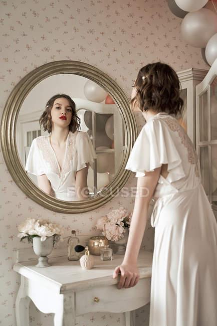 Vista posteriore di magnifica donna con labbra rosse e in vestaglia bianca guardando la fotocamera attraverso il riflesso dello specchio — Foto stock