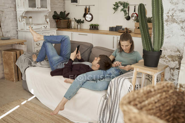Calm thoughtful young man and woman lying on cozy soft couch and surfing mobile phones at home — Stock Photo