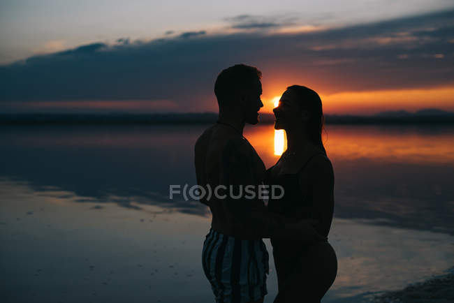 Side view of man and woman on vacation standing in embrace on majestic beach with vibrant crimson sunset sky — Stock Photo