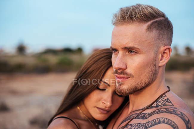 Hemdlos tätowierte männliche und sinnliche Frau im Badeanzug in der Nähe stehen und wegschauen mit blauem Himmel auf dem Hintergrund auf Spanien — Stockfoto
