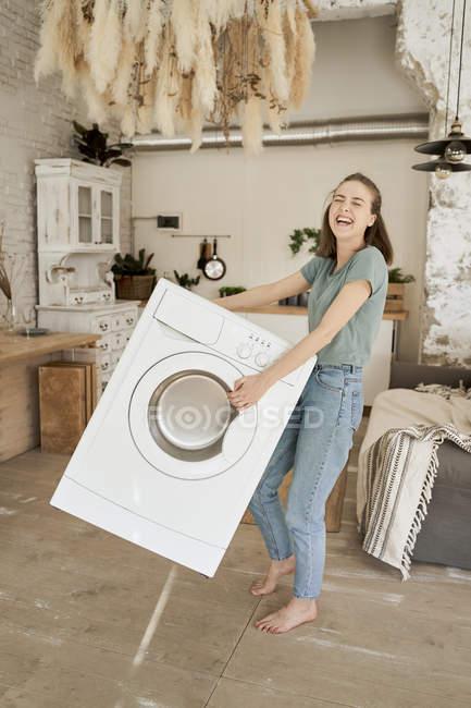 Poderosa mujer joven alegre tratando de llevar lavadora sola en la cocina ligera. - foto de stock