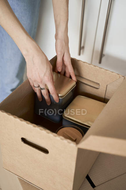 Inreconocible mujer cortada con las manos en posesión de contenedores metálicos fuera de la caja de cartón. - foto de stock