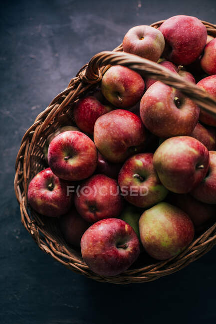 Manzanas rojas frescas sobre mesa oscura y en canasta de mimbre sobre fondo oscuro - foto de stock