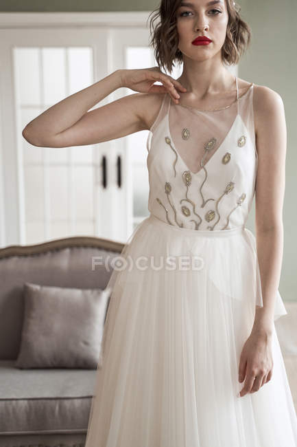 Woman in trendy wedding dress with transparent fabric and golden pattern looking at camera — Stock Photo