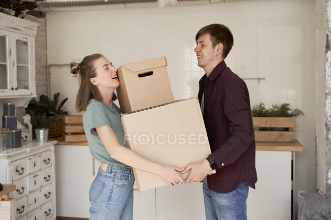 Vista lateral de parejas jóvenes haciendo esfuerzo y portando cajas de cartón con cosas en casa. - foto de stock