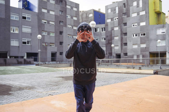 Uomo pensieroso in felpa con cappuccio in piedi guardando la fotocamera tra gli edifici della città sullo sfondo durante la giornata fredda — Foto stock