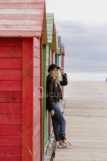 Похмурий довговолосий блондинка у чорній шапці і шкіряній куртці яскраво посміхається до камери і спирається на стіну з дерев'яних пляжних будиночків — стокове фото