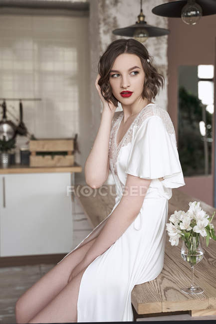 Mulher macia bonita em vestido de seda branca tocando o cabelo e ponderando enquanto sentado na mesa ao lado de flores no apartamento — Fotografia de Stock