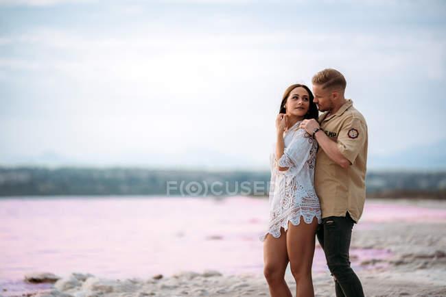 Прекрасна пара стоїть на дивовижному пляжі з рожевою водою і синім небом, тримаючись за руки. — стокове фото