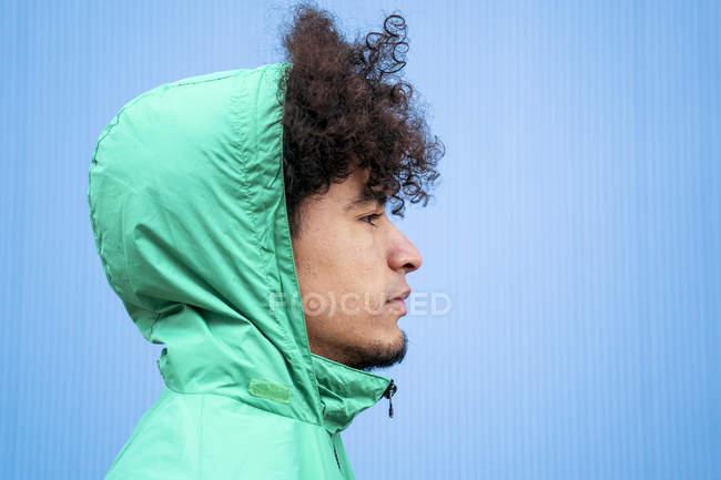 Этнический кудрявый тысячелетний мужчина в зеленой ветровке смотрит в сторону на голубом фоне — стоковое фото