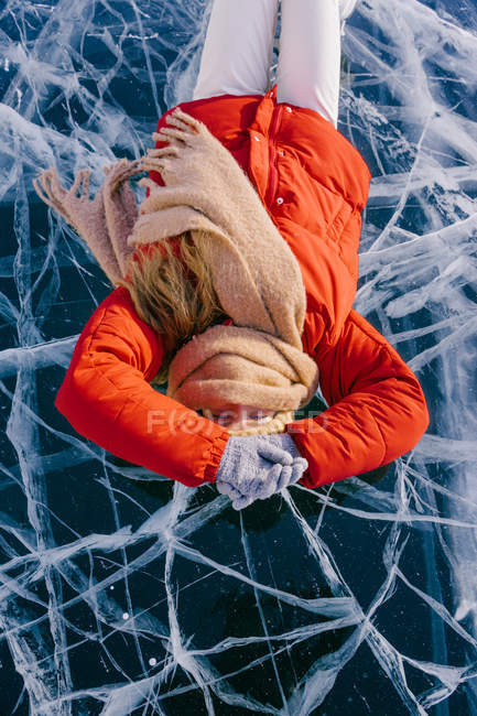 Happy woman in skates lying on ice — Stock Photo