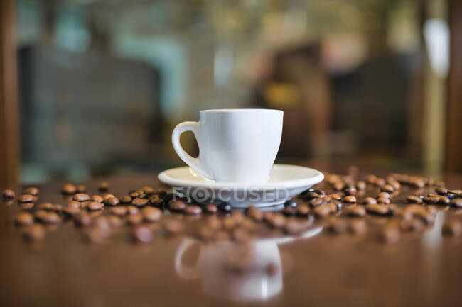 Ceramic cup and coffee beans on wooden table — Stock Photo