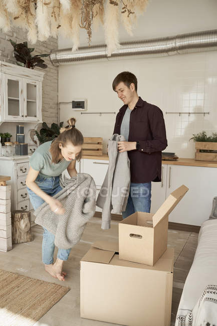 Happy young couple taking out soft gray sweater and things in carton boxes in white light kitchen — Stock Photo