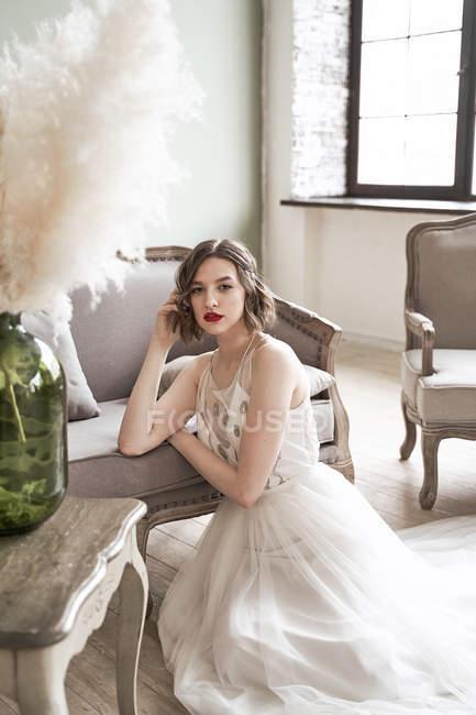 Preciosa mujer con labios rojos en vestido blanco mirando a la cámara mientras está sentada en el suelo junto al sofá - foto de stock