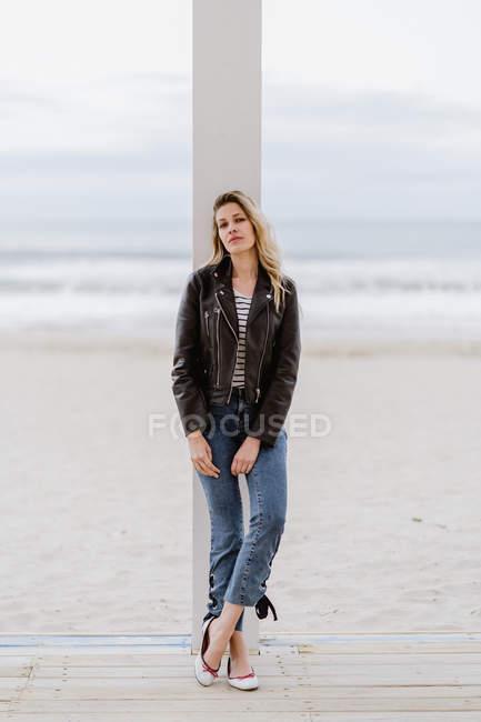 Втішна жінка в чорній шкіряній куртці з упевненістю дивиться на камеру і спирається на білу колону в похмурий день. — стокове фото
