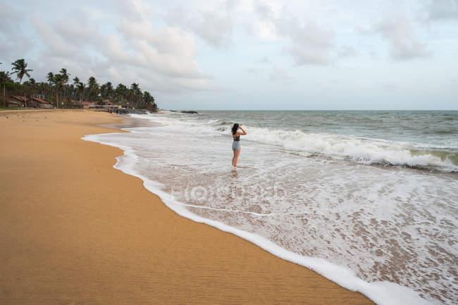 Woman in beachwear walking on sand barefoot — Stock Photo