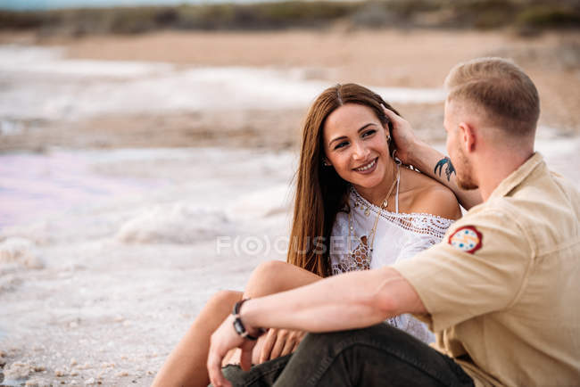 Man touching hair of girlfriend while sitting on an amazing beach of pink water and blue sky holding hands — Stock Photo