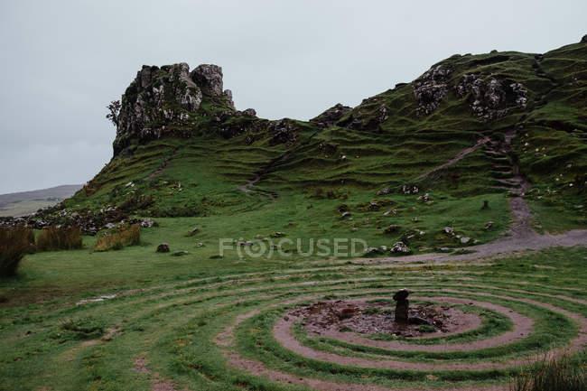 Мирная долина в Шотландии с мистическими кругами на земле в окружении травянистых скалистых холмов — стоковое фото