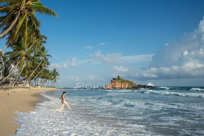 Young woman in water on sand beach with tropical forest — Stock Photo