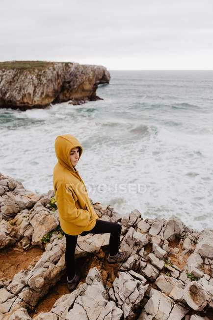 Back view of woman in yellow warm hoodie standing alone on rocky shore with foamy waves on cloudy day — Stock Photo