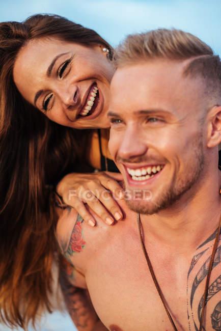 Femme souriante assise sur le dos d'un petit ami tatoué non habillé regardant loin avec le ciel en arrière-plan à Espagne — Photo de stock