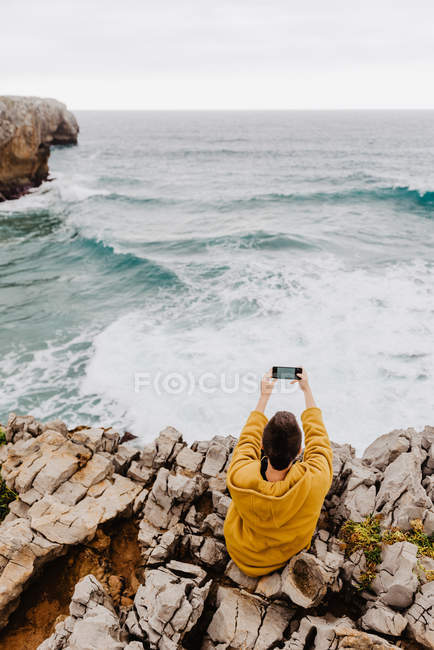 Погляд на коротковолосу жінку в жовтому светрі, що сидить на скелястому узбережжі і вживає наркотики на мобільному телефоні. — стокове фото