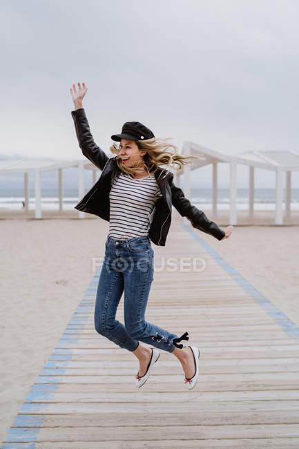 Trendfrau in schwarzer Jacke springt fröhlich mit erhobenen Armen auf weißem Holzsteg mit Ozean im Hintergrund — Stockfoto