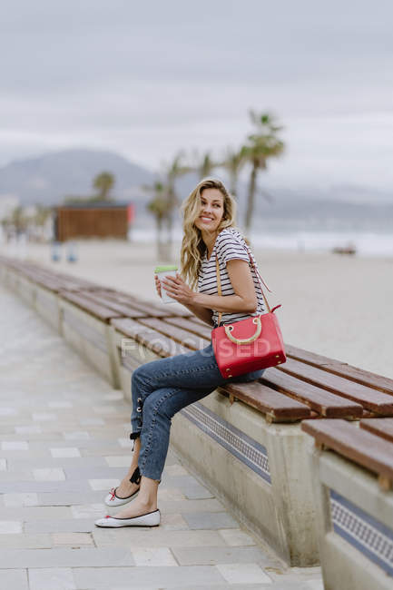 Une jolie femme au beau sourire et à la chemise décontractée rayée qui regarde vers l'extérieur, assise sur un banc — Photo de stock