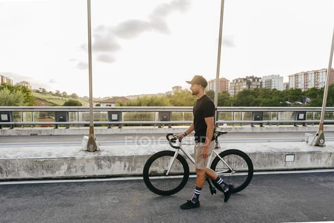 Vista laterale del giovane casuale barbuto ciclista maschile in berretto nero a piedi con bici su strada con edifici della città sullo sfondo — Foto stock