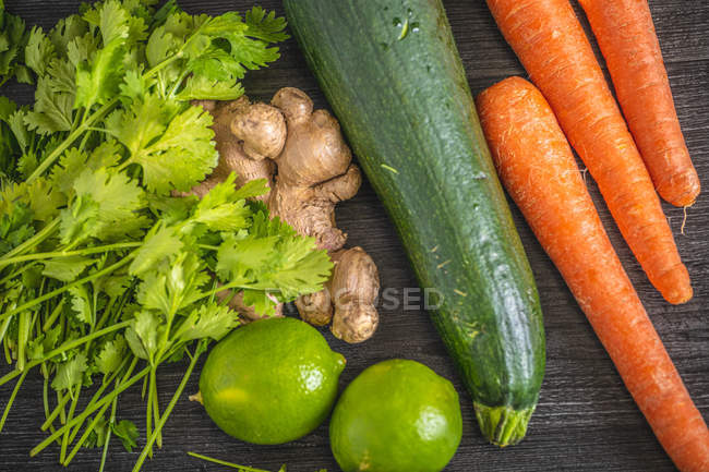 From above orange carrot green zucchini lime and parsley and whole ginger root on table — Stock Photo