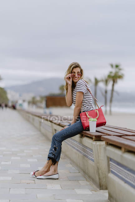 Une jolie femme moderne avec un beau sourire, vêtue d'une chemise à rayures décontractées, regardant par-dessus des lunettes de soleil à la mode, assise sur un banc — Photo de stock