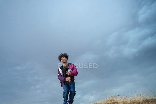 From below of man in stylish sportive colorful clothing standing and looking away with blue sky on background — Stock Photo