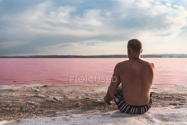 From above of calm fit tattooed man in stylish swimsuit lounging in sun on rocky beach of pink lake at Alicante in Spain — Stock Photo