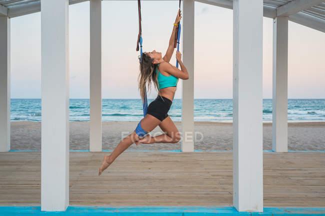 Веселая женщина, растягивающая ногу на голубом гамаке для воздушной йоги на деревянной сцене — стоковое фото