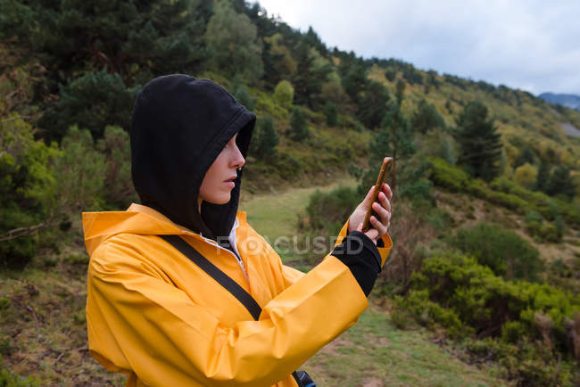Woman in hoodie and yellow raincoat browsing smartphone outdoors — Stock Photo