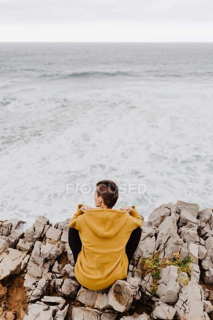 Vue arrière du voyageur en sweat à capuche jaune chaud assis seul sur la rive rocheuse regardant les vagues mousseuses par temps nuageux — Photo de stock
