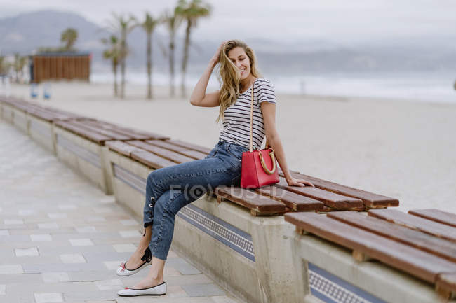 Attractive modern woman with beautiful smile wearing casual striped shirt looking away while sitting at bench — Stock Photo