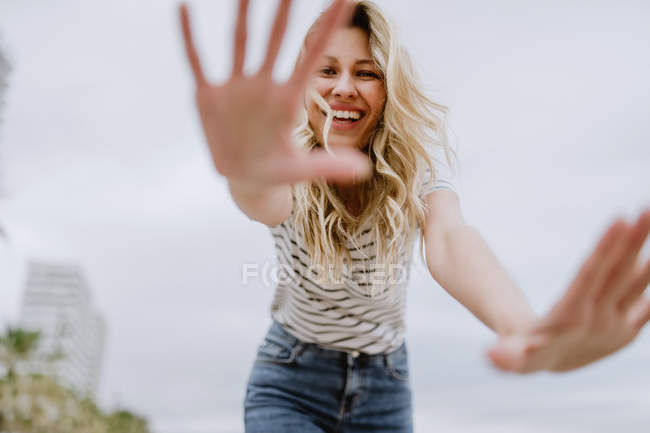 From below of joyful laughing woman in casual clothes spreading hands and hiding face from camera while walking in city — Stock Photo