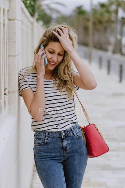 Счастливая веселая женщина в повседневной полосатой рубашке и джинсах стоит рядом со зданием на городской улице и разговаривает по смартфону — стоковое фото