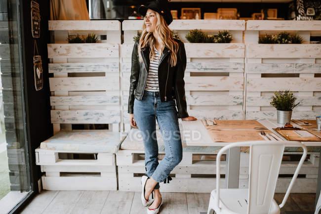 Mujer de pelo largo de moda en chaqueta de cuero y gorra apoyada en la mesa y mirando hacia otro lado - foto de stock