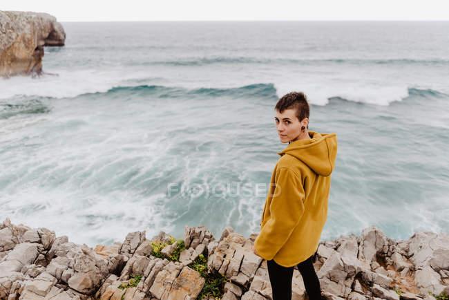 Donna in felpa calda gialla in piedi da sola sulla riva rocciosa con onde schiumose nella giornata nuvolosa e guardando la fotocamera — Foto stock